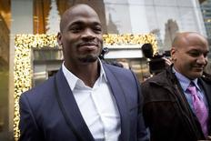 Suspended Minnesota Vikings running back Adrian Peterson (L) exits following his hearing against the NFL over his punishment for child abuse, in  New York December 2, 2014.  REUTERS/Brendan McDermid