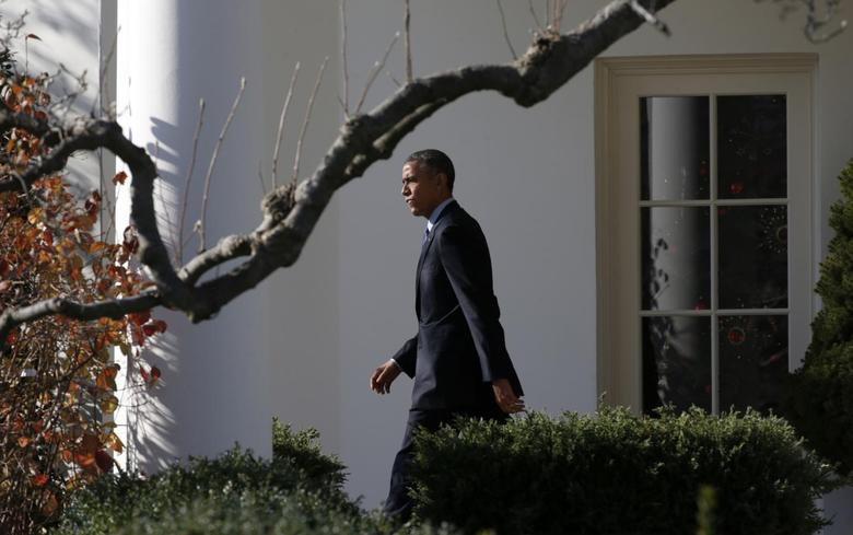 U.S. President Barack Obama walks from the Oval Office as he departs the White House in Washington December 15, 2014.  REUTERS/Kevin Lamarque