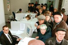 Люди в очереди в одном из банков Красноярска 24 сентября 1998 года. Российские банкиры пожарно пересматривают условия работы с клиентами, повышая стоимость кредитов и депозитов вслед за ночным решением ЦБР взвинтить ставку на 650 базисных пунктов до 17 процентов с целью сдержать давление на рубль. REUTERS