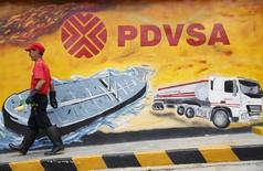 A worker walks past a mural with a PDVSA logo at its gas station in Caracas August 29, 2014. REUTERS/Carlos Garcia Rawlins