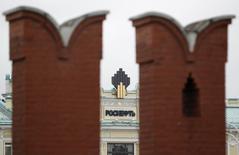 Логотип Роснефти на её штаб-квартире на фоне зубцов стены московского Кремля 27 мая 2013 года. Роснефть должна погасить $7,6 миллиарда из бридж-кредита, выданного ей два года назад на покупку TНK-BP, сообщили RLPC банкиры, близкие к сделке. REUTERS/Sergei Karpukhin