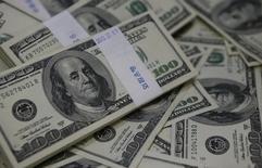 Долларовые купюры в банке в Сеуле 2 августа 2013 года. Курс доллара к корзине шести основных валют снижается после 1-процентного роста, вызванного заявлением ФРС по итогам ежемесячного совещания. REUTERS/Kim Hong-Ji