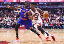 Chicago Bulls guard Jimmy Butler (21) dribbles the ball against New York Knicks guard Tim Hardaway Jr. (5) during the second half at United Center. The Chicago Bulls defeat the New York Knicks 103-97. Mandatory Credit: Mike DiNovo-USA TODAY Sports