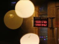 Bывеска с курсом рубля в центре Москвы 18 декабря 2014 года. Рубль торгуется в плюсе при открытии торгов пятницы в надежде на продажи экспортной выручки под уплату налогов и эффект от комплекса мер Центробанка и правительства по стабилизации валютного рынка, однако его рост может быть неустойчив - в условиях свободного плавания рубля и крайне низкой рыночной ликвидности любые более-менее крупные локальные покупки валюты в моменте значительно меняют котировки. REUTERS/Maxim Zmeyev