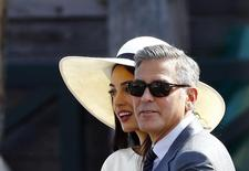 U.S. actor George Clooney and his wife Amal Alamuddin leave Venice city hall after a civil ceremony to formalize their wedding in Venice September 29, 2014. REUTERS/Stefano Rellandini/Files