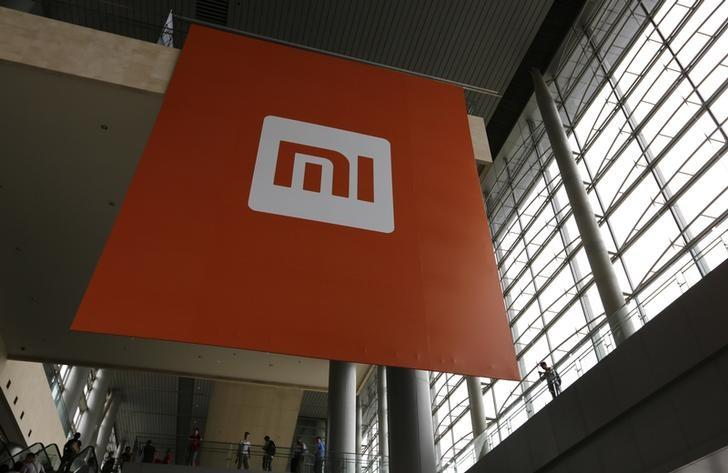 People stand near a logo of Xiaomi ahead of the launching ceremony of Xiaomi Phone 4, in Beijing, July 22, 2014. Picture taken July 22, 2014. REUTERS/Jason Lee