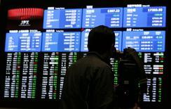 Оператор снимает у экрана с котировками на Токийской фондовой бирже 15 декабря 2014 года. Азиатские фондовые рынки выросли в понедельник вслед за Уолл-стрит и нефтяным рынком. REUTERS/Yuya Shino