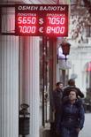 Женщина проходит мимо вывески пункта обмена валют в Москве 19 декабря 2014 года. Рубль дорожал более чем на 7 процентов к доллару США до отметки 54,26, впервые с 10 декабря, за счет продаж экспортной выручки под уплату крупных налогов и отсутствия крупных покупателей валюты за рубли, в том числе в условиях напряженной ситуации с ликвидностью на денежном рынке. REUTERS/Eduard Korniyenko