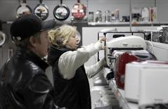 Люди выбирают технику в магазине в Ставрополе 17 декабря 2014 года. Россияне в неделю экстремального обесценения рубля потратили на электронику и одежду в 2,5-3,5 раза больше, чем годом ранее, свидетельствуют данные банка ВТБ 24, который входит в число крупнейших банков-эквайеров в РФ. REUTERS/Eduard Korniyenko