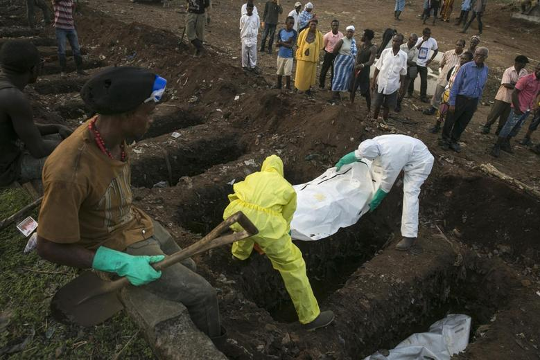 A grave digger watches as health workers carry the body of an Ebola victim for burial at a cemetery in Freetown December 17, 2014. REUTERS/Baz Ratner