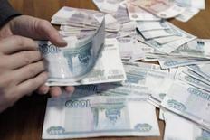 Сотрудник ставропольской компании считает рубли 17 декабря 2014 года. Правительство направило госкомпаниям-экспортерам директиву о сокращении валютной позиции, а ЦБР обсуждает с ними план равномерной продажи выручки в течение года. REUTERS/Eduard Korniyenko