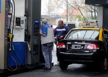 Un taxista cargando combustible en una gasolinera en Buenos Aires, jul 31 2014. El Gobierno de Argentina bajará un 7 por ciento el valor del barril de crudo, a 78 dólares del barril, tras alcanzar un acuerdo con provincias productoras de hidrocarburos, dijo el lunes un líder sindical de los trabajadores petroleros presente en una reunión entre ambas partes. REUTERS/Enrique Marcarian