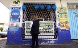 Una mujer en su tienda de teléfonos móviles en Ciudad de México, oct 20 2009. México dijo el martes que espera recibir en enero los primeros reportes de pruebas de tecnologías de alta velocidad para telecomunicaciones inalámbricas en una banda del espectro radioeléctrico que ha destinado a un ambicioso proyecto de red compartida. REUTERS/Daniel Aguilar