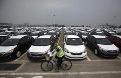 A worker cycles past cars made by South Korea's biggest automakers Hyundai Motor Co and sister company Kia Motors at the company's shipping yard at a port in Pyeongtaek July 21, 2014. REUTERS/Kim Hong-Ji
