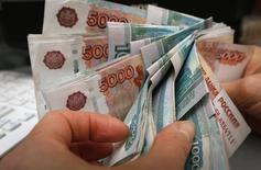 Un empleado cuenta rublos rusos en un local comercial en Krasnoyarsk, 26 diciembre, 2014. La moneda rusa subía el viernes a sus niveles más altos en más de tres semanas, en medio de una fuerte recuperación tras tocar recientemente mínimos históricos después de que el Gobierno ordenara a los exportadores vender parte de sus ingresos en divisas fuertes. REUTERS/Ilya Naymushin