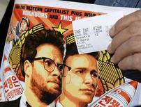 """Homem segura entrada e pôster do filme """"A Entrevista"""", em Los Angeles. 25/12/2014 REUTERS/Kevork Djansezian"""