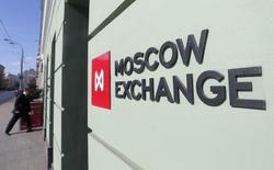 Мужчина заходит в помещение Московской биржи 14 марта 2014 года. Торги российскими акциями начались в понедельник разнонаправленно: индекс РТС падает вслед за рублем, а ММВБ прибавляет более одного процента. REUTERS/Maxim Shemetov