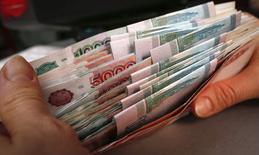Сотрудник магазина пересчитывает купюры в Красноярске 26 декабря 2014 года. Рубль начал торги понедельника снижением к доллару и евро, отыгрывая падение нефтяных котировок ниже $60, участники торгов выходят из рубля, видя риски перед длинными новогодними выходными в РФ. REUTERS/Ilya Naymushin