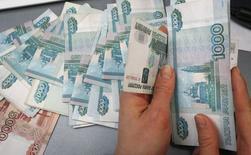 Un empleado cuenta rublos rusos en un local en Krasnoyarsk. Imagen de archivo, 26 diciembre, 2014. La economía de Rusia se contrajo en noviembre por primera vez desde octubre de 2009, en la señal más fuerte a la fecha del impacto que tienen las sanciones occidentales y el desplome de los precios del petróleo.  REUTERS/Ilya Naymushin