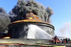 Bomberos intentan contener un incendio en el puerto petrolero de Es Sider in Ras Lanuf, Libia, dic 29 2014. Dos depósitos de almacenamiento de petróleo siguen en llamas en el puerto libio de Es Sider, mientras que otros dos fueron destruidos casi una semana después de que enfrentamientos en la terminal ocasionaran el incendio, dijo el martes el portavoz de la estatal National Oil Corp (NOC).  REUTERS/Stringer