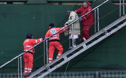 """Passageiro ferido recebe ajuda para desembarcar do cargueiro """"Spirit of Piraeus"""" em Bari, na Itália, depois que a balsa """"Norman Atlantic"""" pegou fogo na costa da Grécia, na segunda-feira. 29/12/2014 REUTERS/Yara Nardi"""