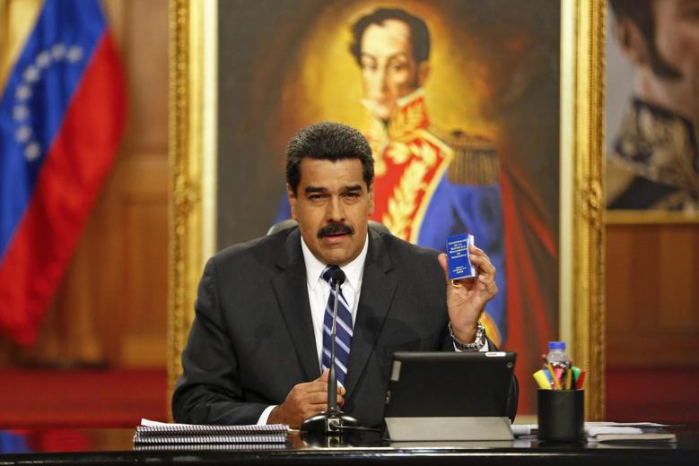 Venezuela's President Nicolas Maduro holds a copy of the country's constitution as he speaks during a news conference at Miraflores Palace in Caracas December 30, 2014. REUTERS/Carlos Garcia Rawlins