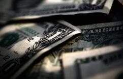 Долларовые купюры в Торонто 26 марта 2008 года. Доллар готовится к тому, чтобы завершить 2014 год ростом на 12 процентов к корзине валют, а ожидаемое повышение ставки ФРС США может усилить его привлекательность в новом году. REUTERS/Mark Blinch