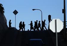 Personas caminan hacia su lugar de trabajo en Los Angeles. Imagen de archivo, 13 mayo, 2014. El número de estadounidenses que presentaron por primera vez el pedido del beneficio por desempleo subió más de lo previsto la semana pasada, pero no lo suficiente como para cambiar la visión de un fortalecimiento sostenido en el mercado laboral. REUTERS/Mike Blake