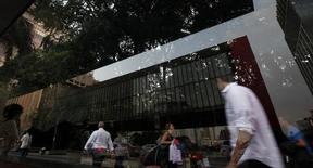 Reflejo de personas caminando por Avenida Paulista, en el distrito financiero de Sao Paulo. Imagen de archivo, 8 abril, 2014.  La actividad en el sector de servicios de Brasil cayó en diciembre por tercer mes consecutivo, afectada por la debilidad de la moneda y por un creciente escándalo de corrupción en la petrolera estatal Petrobras. REUTERS/Paulo Whitaker