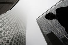 A man walks past a building in the morning mist at London's financial district of Canary Wharf September 16, 2014.   REUTERS/Kevin Coombs