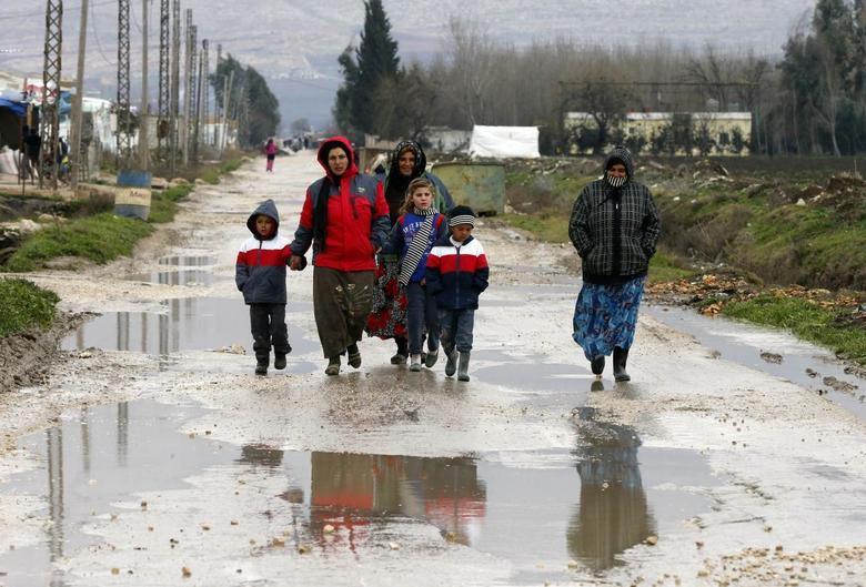 Syrian refugees walk along a makeshift settlement in Bar Elias in the Bekaa valley January 5, 2015. REUTERS/Mohamed Azakir