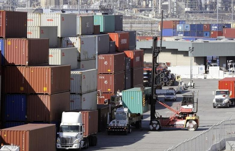 A truck is loaded with a shipping container at the Port of Los Angeles October 27, 2014. REUTERS/Bob Riha Jr.
