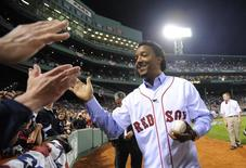 Former Boston Red Sox pitcher Pedro Martinez slaps hands with fans before MLB's 2010 season opener between the reigning World Series Champions New York Yankees and the Red Sox in their American League baseball game at Fenway Park in Boston, Massachusetts April 4, 2010. REUTERS/Gretchen Ertl