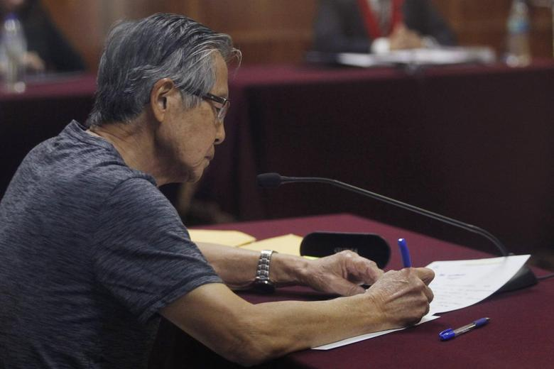 Peru's former President Alberto Fujimori writes notes as he sits in court during the sentencing in his trial on charges of embezzling state funds to manipulate the media during his tenure as president, in Lima January 8, 2015. REUTERS/Enrique Castro-Mendivil