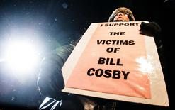 A woman protests against Bill Cosby, outside the Centre In The Square venue where the comedian is performing, in Kitchener, January 7, 2015. REUTERS/Mark Blinch