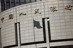 """La sombra de una bandera china vista en el frontis del banco central chino en Beijing. Imagen de archivo, 24 noviembre, 2014. El banco central chino seguirá manteniendo una política monetaria """"prudente"""" en 2015, con un crecimiento estable del crédito y libertad para realizar ajustes a la política cuando sea necesario, dijo el regulador en un comunicado en Internet el viernes. REUTERS/Kim Kyung-Hoon"""