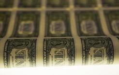Una lámina de dólares estadounidenses durante su etapa de producción en Washington. Imagen de archivo, 14 noviembre, 2014. El dólar recortó sus pérdidas el lunes tras un dato mejor al esperado sobre el empleo en Estados Unidos en diciembre, que dejó intactas las expectativas de que la Reserva Federal suba este año sus tasas de interés, lo que daría más fortaleza al billete verde. REUTERS/Gary Cameron