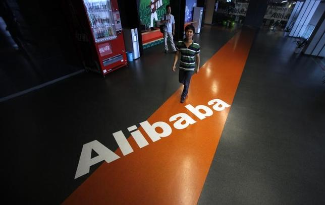An employee walks pass a logo of Alibaba during a media tour organised by government officials at its headquarters on the outskirts of Hangzhou, Zhejiang province, June 20, 2012. Picture taken June 20, 2012. IPO/YAO REUTERS/Carlos Barria/Files