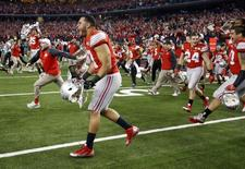 Jan 12, 2015; Arlington, TX, USA; Ohio State Buckeyes players rush the field after defeating the Oregon Ducks in the 2015 CFP National Championship Game at AT&T Stadium. Matthew Emmons-USA TODAY Sports