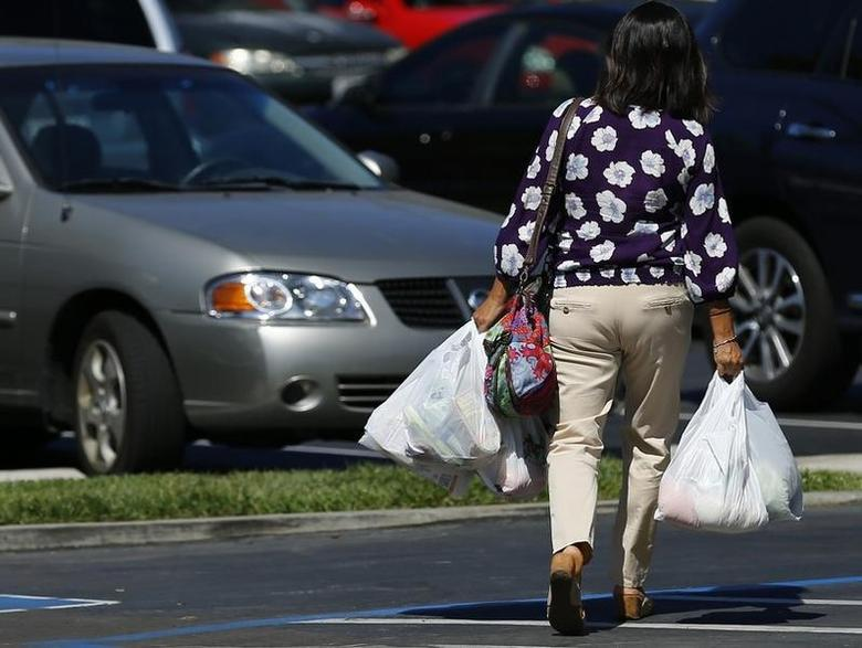 A shopper carries her groceries to her car after shopping at a grocery store in San Diego, California September 30, 2014. REUTERS/Mike Blake