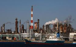 A ship passes a petro-industrial complex in Kawasaki near Tokyo December 18, 2014. Brent crude held steady above $61 a barrel on Thursday, bringing a sharp drop in prices to a temporary halt as companies are forced to cut upstream investments around the world. REUTERS/Thomas Peter (JAPAN - Tags: BUSINESS ENERGY MARITIME)