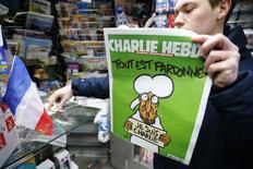 ATENCIÓN EDITORES, ESTA IMAGEN PUEDE RESULTAR OFENSIVA.   Un hombre sujeta la nueva edición de Charlie Hebdo frente a un kiosko en París, 14 enero, 2015.  La primera edición de Charlie Hebdo publicada tras los ataques mortales llevados a cabo por yihadistas en París se agotó en cuestión de minutos en muchos quioscos en toda Francia el miércoles, con colas para comprar copias y apoyar al semanario satírico. REUTERS/Stephane Mahe