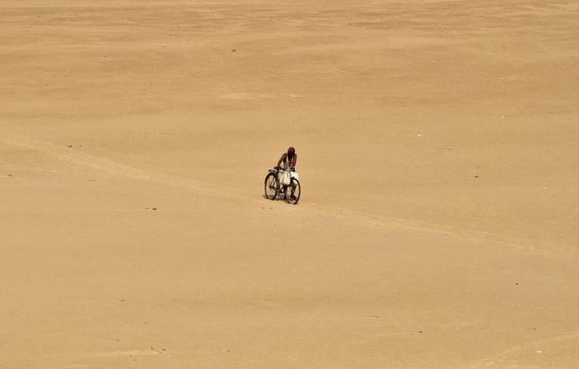 A villager with his bicycle walks on the banks of the Kuakhai River on a hot summer day, on the outskirts of eastern Indian city of Bhubaneswar June 9, 2014.  REUTERS/Stringer