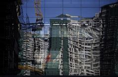 Reflet d'un immeuble en construction à Pékin. Le ralentissement de la croissance de l'économie chinoise va se poursuivre cette année en raison du manque d'élan du crédit, de la chute de l'immobilier et de la faiblesse de la demande globale, montre une enquête Reuters. La croissance du produit intérieur brut de la Chine devrait s'établir à 7% cette année et tomber à 6,8% en 2016. /Photo prise le 15 décembre 2014/REUTERS/Kim Kyung-Hoon