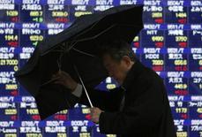 Una persona sujera un paraguas mientras pasa frente una pantalla electrónica que muestra índices económicos en Tokio. Imagen de archivo, 15 enero, 2015. Las bolsas chinas retrocedían el lunes después de que los reguladores tomaron medidas para frenar los préstamos especulativos en el país, y los inversores globales se mostraban cautelosos antes de una reunión clave del consejo del Banco Central Europeo. REUTERS/Yuya Shino