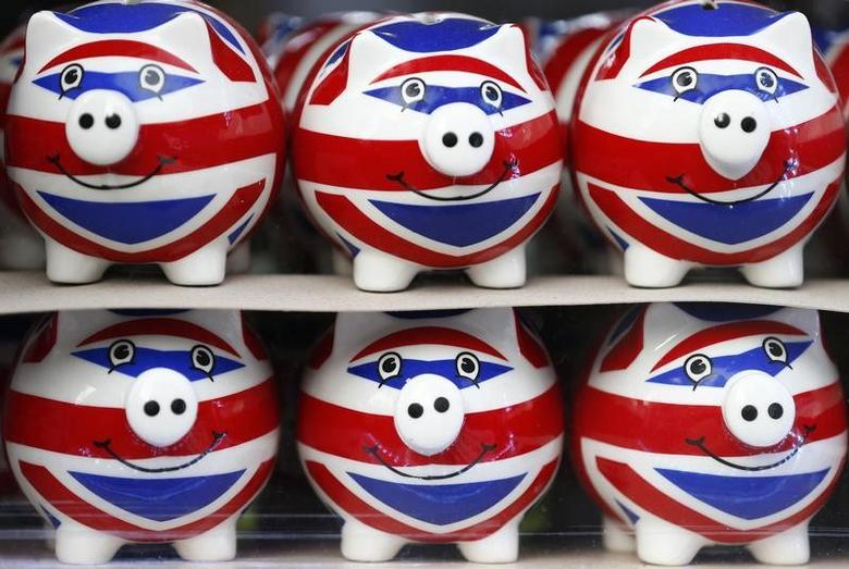 Smiling Union Jack piggy banks are lined up for sale in the window of a souvenir store on Oxford Street in central London January 20, 2014.  REUTERS/Andrew Winning