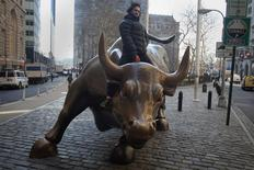 "A tourist mounts the ""Charging Bull"" statue as he poses for a photo near Wall Street, in the Manhattan borough of New York January 16, 2015. REUTERS/Carlo Allegri"