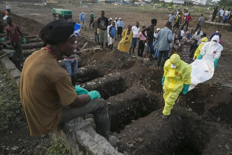 A grave digger watches as health workers carry the body of an Ebola victim for burial at a cemetery in Freetown, Sierra Leone, December 17, 2014. REUTERS/Baz Ratner