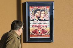 """Un hombre camina frente un afiche de la película """"The Interview"""" a las afueras del teatro Alamo Drafthouse en Littleton, Colorado. 23 de diciembre de 2014.  REUTERS/Rick Wilking"""
