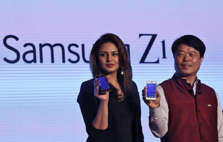 Hyun Chil Hong (R), president and chief executive of Samsung India Electronics, and Bollywood actress Huma Qureshi hold the Samsung's new Z1 smartphones at its launch in New Delhi January 14, 2015.    REUTERS/Adnan Abidi